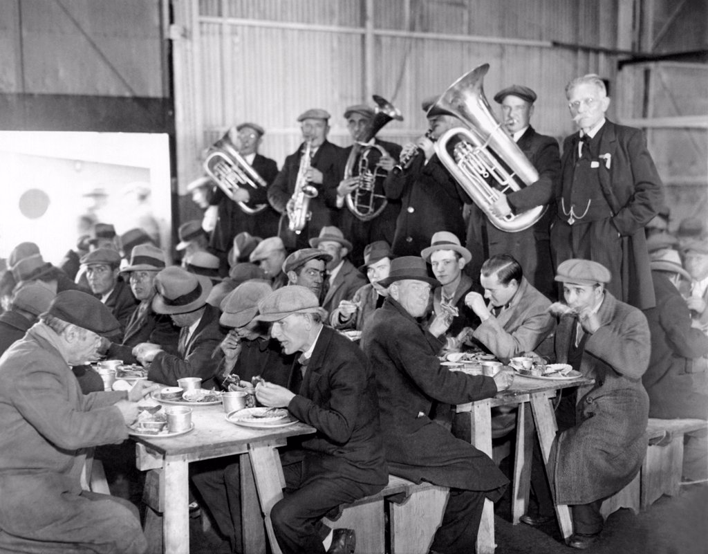 Stock Photo: 4048-9563 Municipal Lodging House Thanksgiving dinner. The hungry and destitute of New York City eat their free thanksgiving dinner accompanied by a brass band. Nov. 28, 1932.