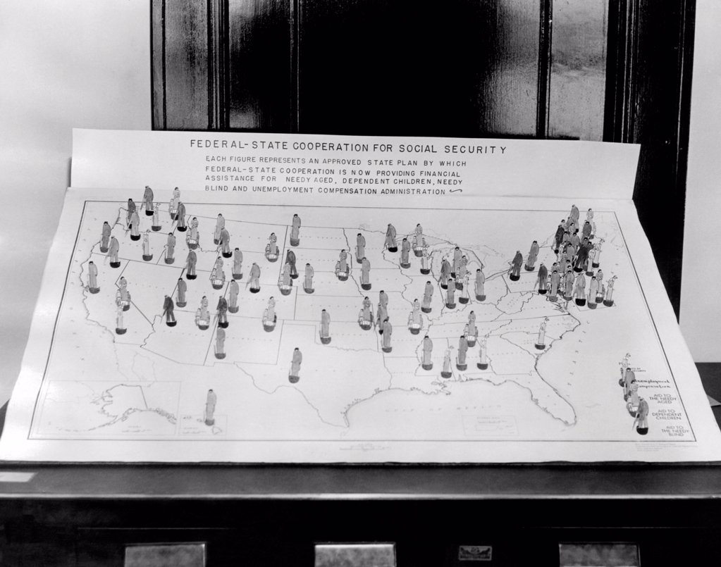 Stock Photo: 4048-9564 Social Security Board ready to operate. 1936 map shows figures representing an approved state plan by which Federal-State cooperation is now providing financial assistance to needy aged, dependent children, needy blind, and unemployed. Nov. 14, 1936.