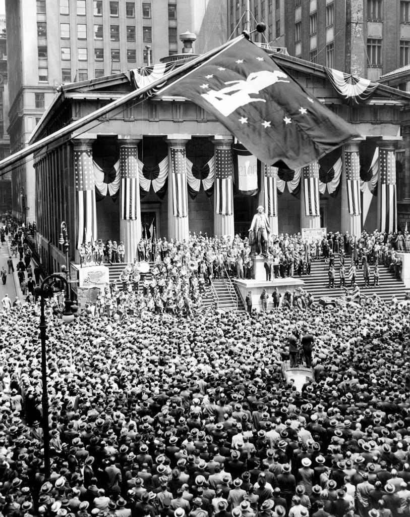 Stock Photo: 4048-9608 The New York Stock Exchange celebrates its 150th anniversary with the greatest war bond rally in the city's history. The war bond flag waves above the statue of George Washington at the Subtreasury Building. May 8, 1942.