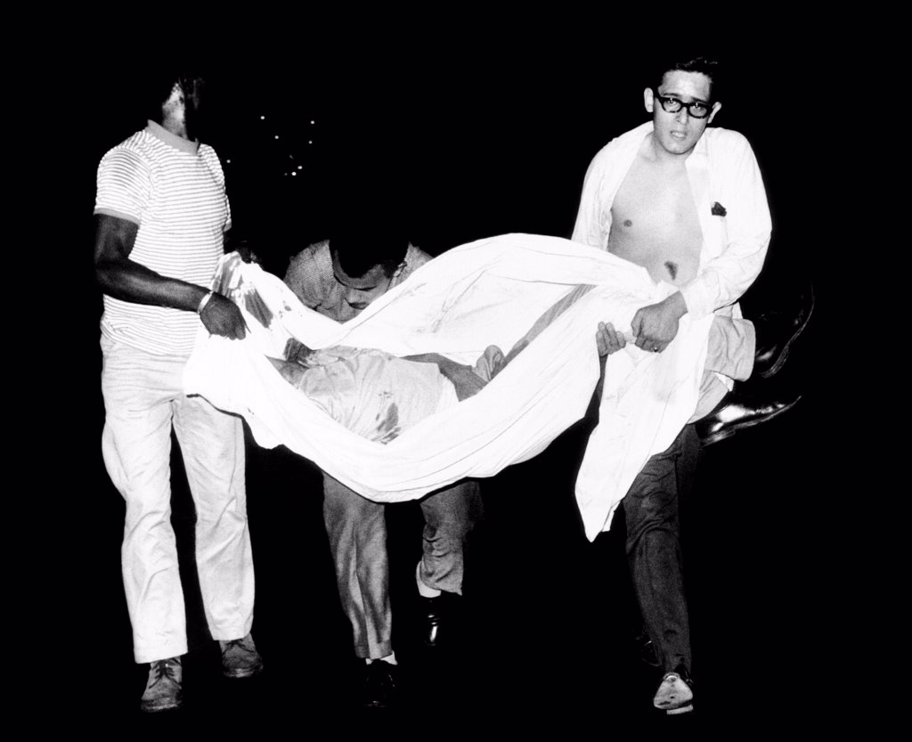 Three men carry body of a youth who died after apparently falling from a rooftop during third night of civil disorder in Spanish Harlem on July 25, 1967. : Stock Photo