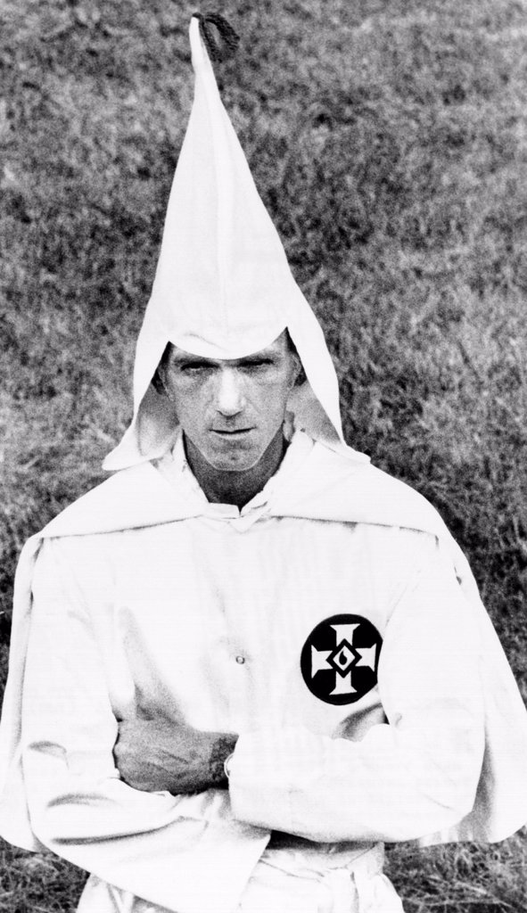 Ku Klux Klansman folds his arms in a traditional Klan posture at a cross burning at a small farm near Indianapolis. July 25, 1975. : Stock Photo