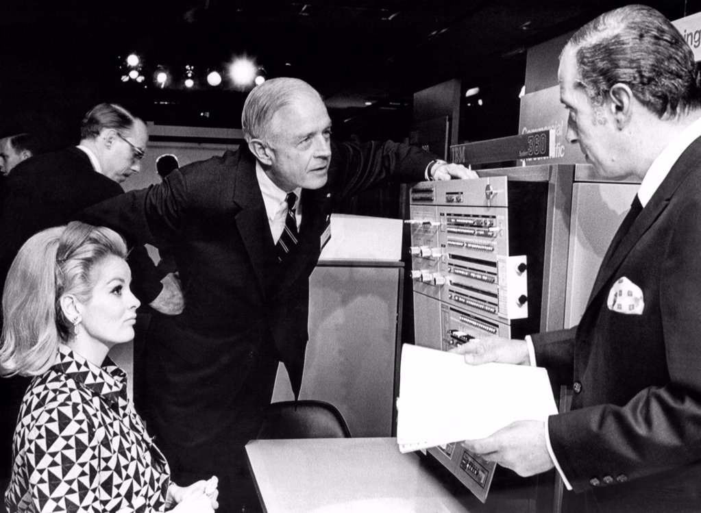 Stock Photo: 4048-9669 Thomas J. Watson, Jr., talks with IBM stockholders before their yearly meeting in the New York Coliseum. The IBM system/360 40 model was on display. April 24, 1967.