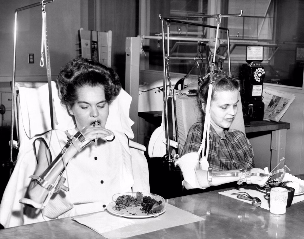 Stock Photo: 4048-9672 Two young women in rehabilitation after polio. They were both in Iron Lungs and are now feeding themselves with the help of special equipment. Rancho Los Amifos Respiratory Center in Hondo California. Dec. 27, 1954.