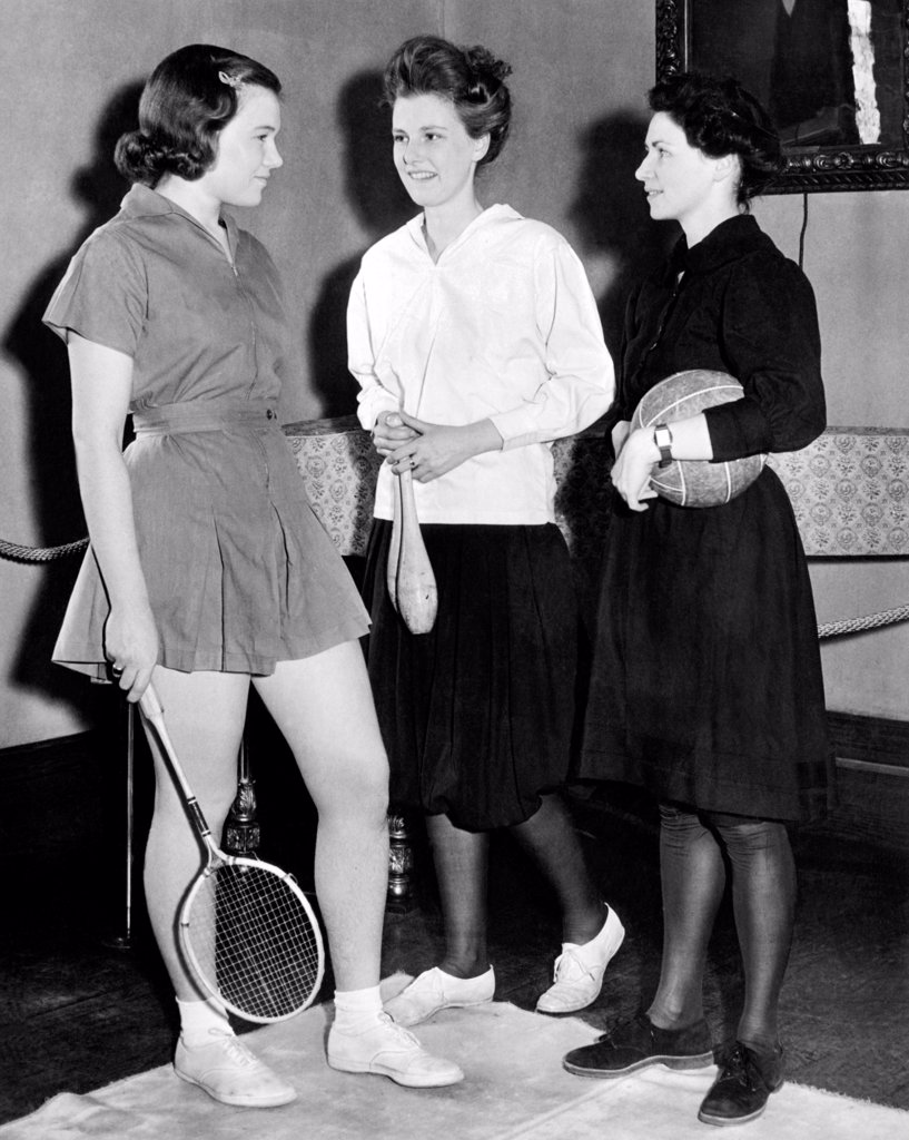 Stock Photo: 4048-9750 Student gym suits have changed over time. From a Barnard College exhibit: L-R: Deborah Allen wears a contemporary short skirted suit of 1939, Ingrid Bach wears bloomers from 1905, and Ruth Cummings wears a 1895 gym dress. Feb. 1939.