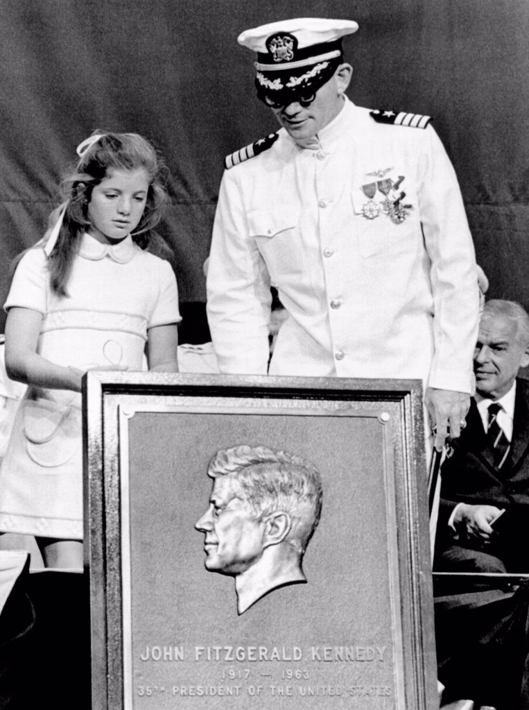 Stock Photo: 4048-9806 Caroline Kennedy with Capt. Earl Yates, commander of the newly commissioned aircraft carrier, USS John F. Kennedy. She presented him with a commemorative relief of her father, President John F. Kennedy. July 27, 1968.