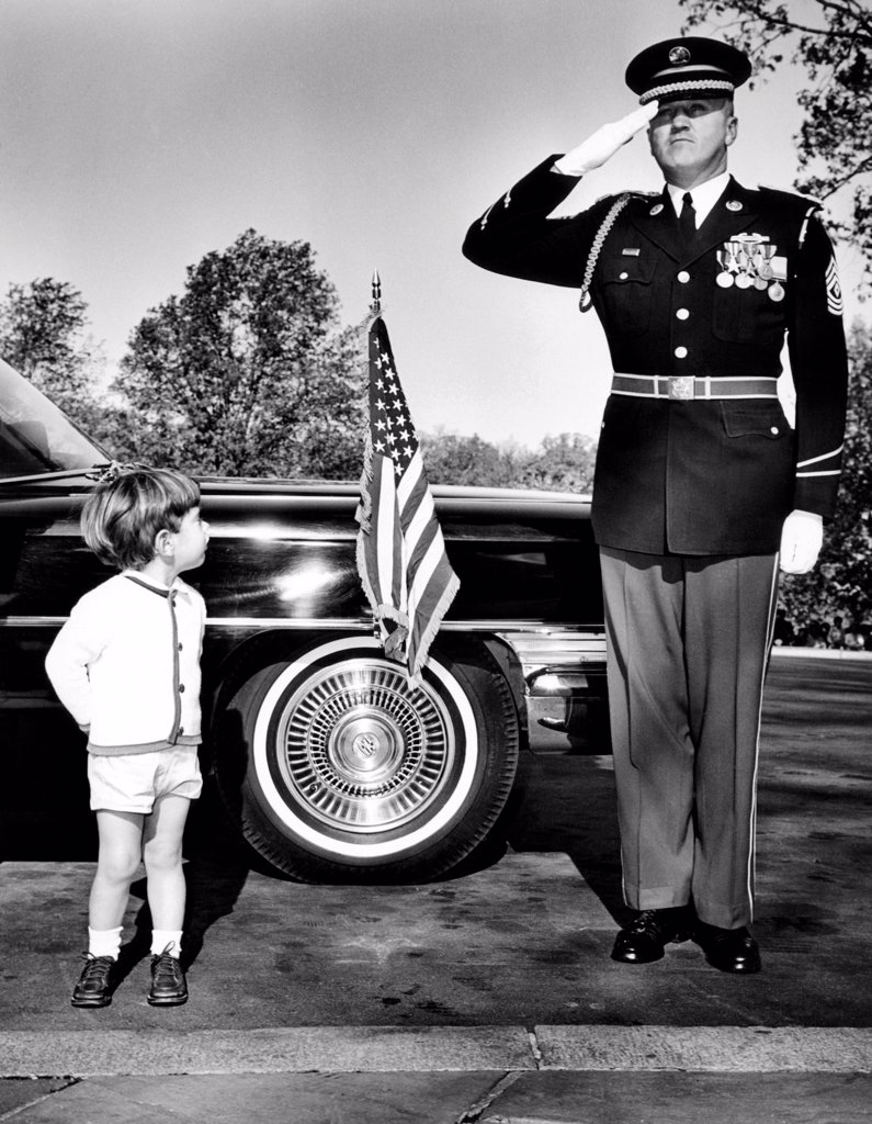 John F. Kennedy Jr. look up at Sgt. Eldon J. Johnston, during Veteran's Day ceremonies at Arlington National Cemetery. Nov. 11, 1963. : Stock Photo