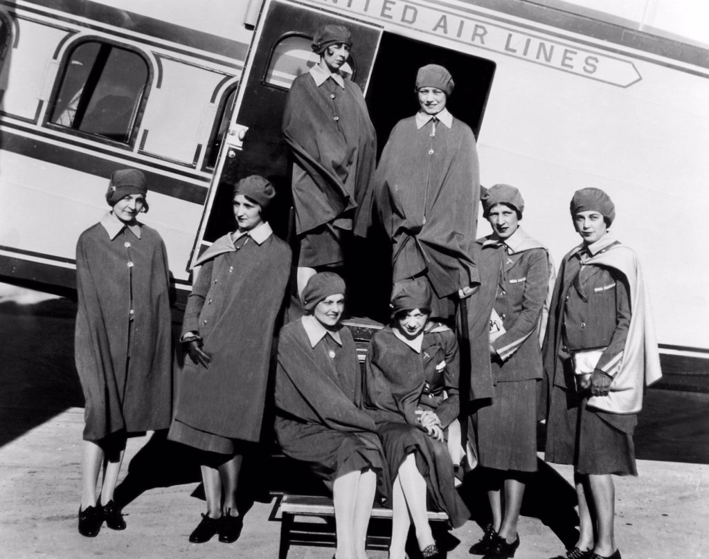Stock Photo: 4048-987 Some of the first stewardesses for United Airlines, known as 'skygirls', standing next to a Boeing tri-motored plane, 1930
