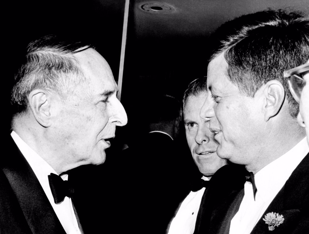 Stock Photo: 4048-9891 President Kennedy talks with Gen. Douglas MacArthur (left). They were at the National Football Hall of Fame dinner at the Waldorf Astoria. In his speech, the President lamented that America's number one national sport seems to be sitting and watching somebody else get exercise. Dec. 5, 1961.