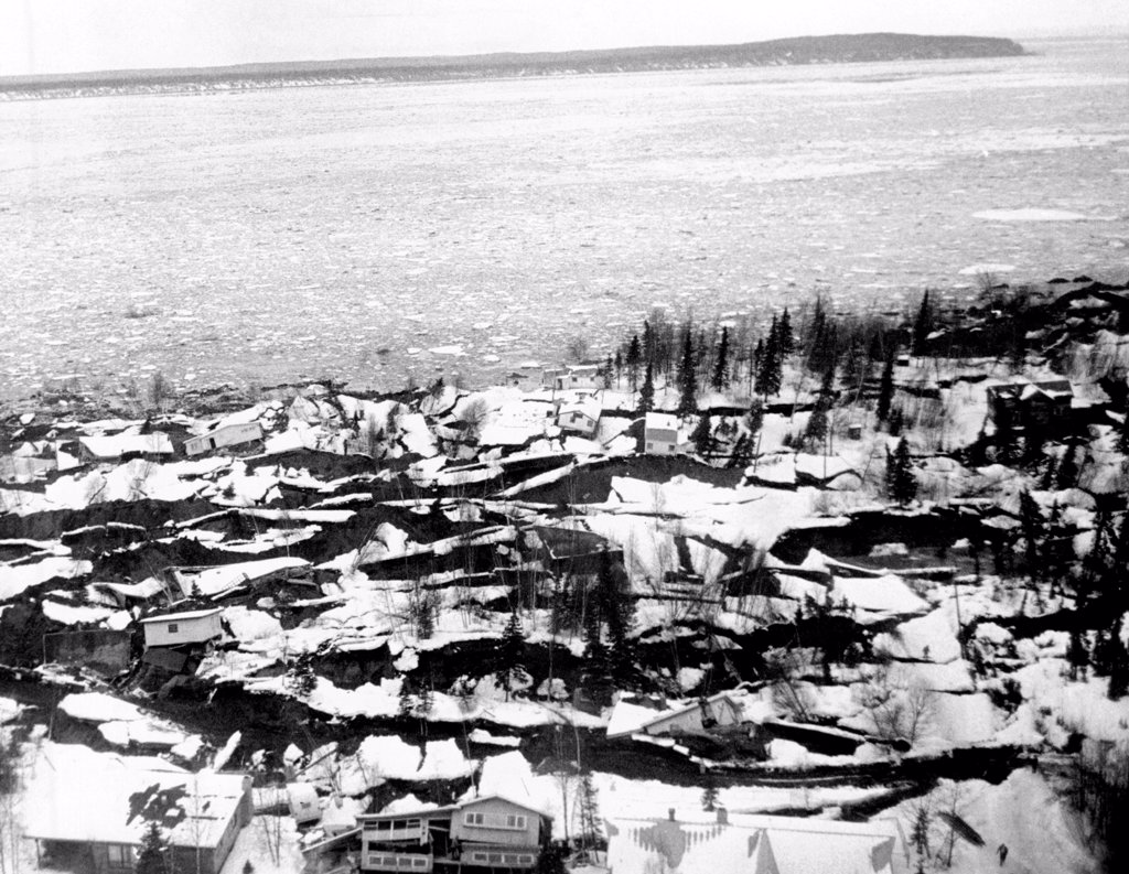 Stock Photo: 4048-9968 1964 Alaska Earthquake. Aerial view of the Anchorage residential area of Turnagail shows destruction caused by the up thrust of the Good Friday earthquake. The jagged striations are newly exposed earth. The snow-covered earth was the Pre-Earthquake surfaces. In background is ice-covered Cook inlet. March 27, 1964