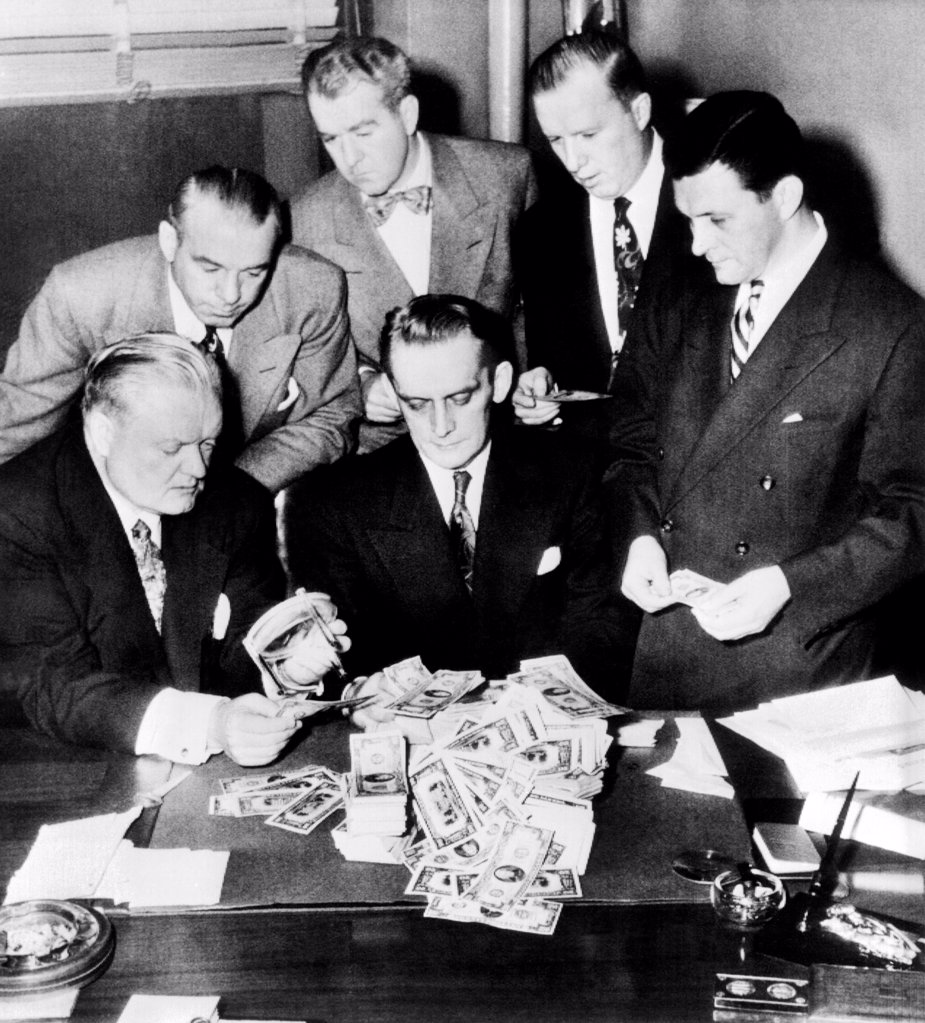 Federal and State men looking at part of $100,000 of counterfeit money seized in Chicago, Feb, 2, 1952. Seated (L- R): John Boyle, States Atty, Harry Anheier, Chief of Secret Service, Standing, Lt. James Oakey, States Atty., Investigator, Everett J. Ryan, U.S. Asst. Atty., Tom Mclnerney, States Investigator, and Otto Kerner Jr., U.S. Dist. Atty. : Stock Photo