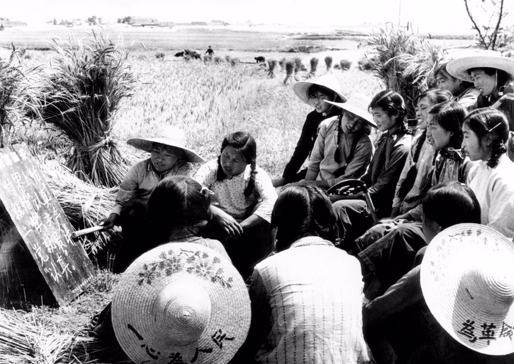 Chinese Communist Cultural Revolution propaganda during a work break. The women field workers of the Fanghsiang Production Brigade study a quotation of Chairman Mao, 'What really counts in the World is conscientiousness, and the Communist Party is most particular about being conscientious.' Oct. 1966. : Stock Photo