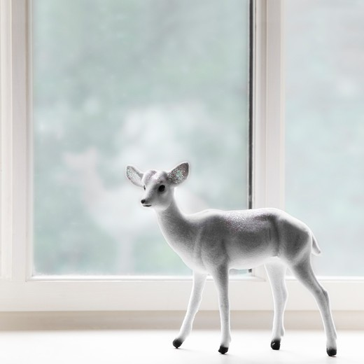 Close-up of a figurine of a fawn at a window sill : Stock Photo