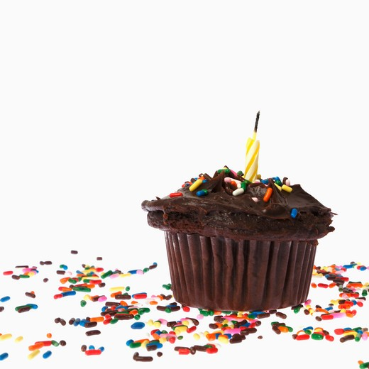 Cupcake with a candle and sprinkles : Stock Photo