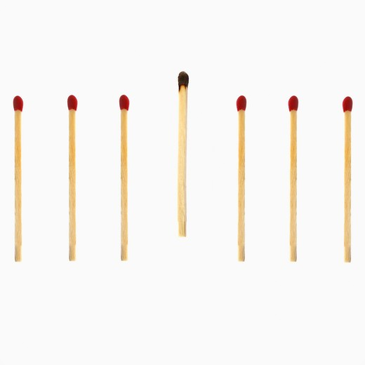 Close-up of a burnt matchstick with red matchsticks : Stock Photo