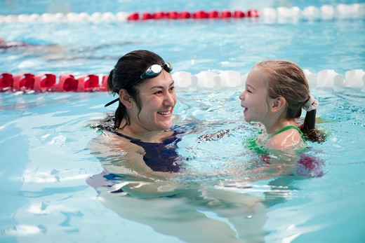 Stock Photo: 4050-111 Woman and her daughter swimming in a pool