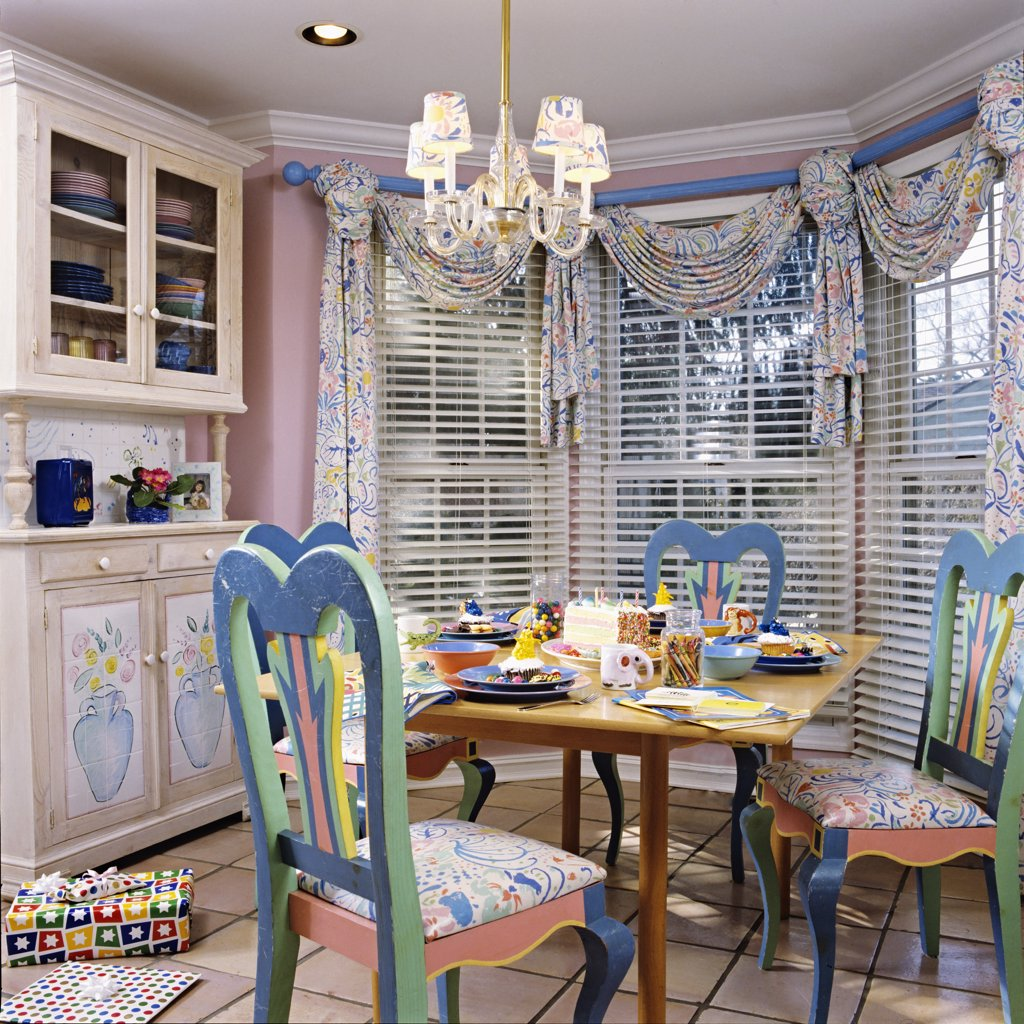 EATING AREA: Near kitchen. Pastel painted chairs, birthday party, table setting, chandelier, swag and jabot curtains with blinds, crown molding, display cupboard, tile floor. : Stock Photo