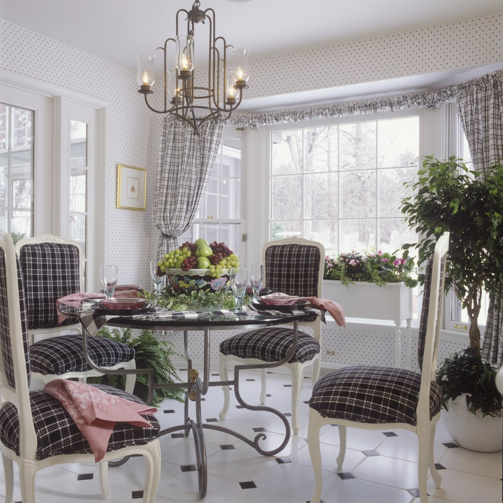 DINING ROOM: Round glass table with scroll iron base, French style side chairs, painted white wood, upholstered  in black and white plaid, bowl of fruit, chandelier, small patterned wallpaper, plaid tie back curtains, covered drapery rod, bay window, white planter, glassware, black and white tile floor : Stock Photo