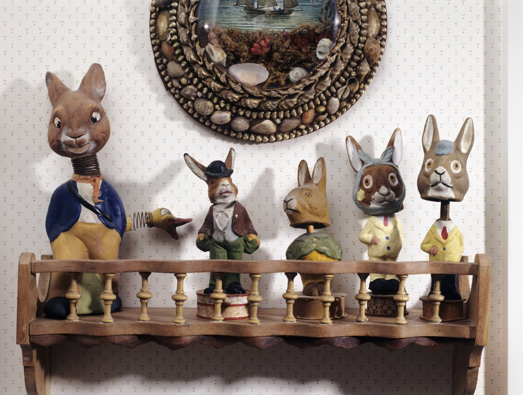 COLLECTIONS: ENID HUBBARD RABBITS: Wooden spool shelf holds five paper mache nodder rabbits, shell art hangs above : Stock Photo