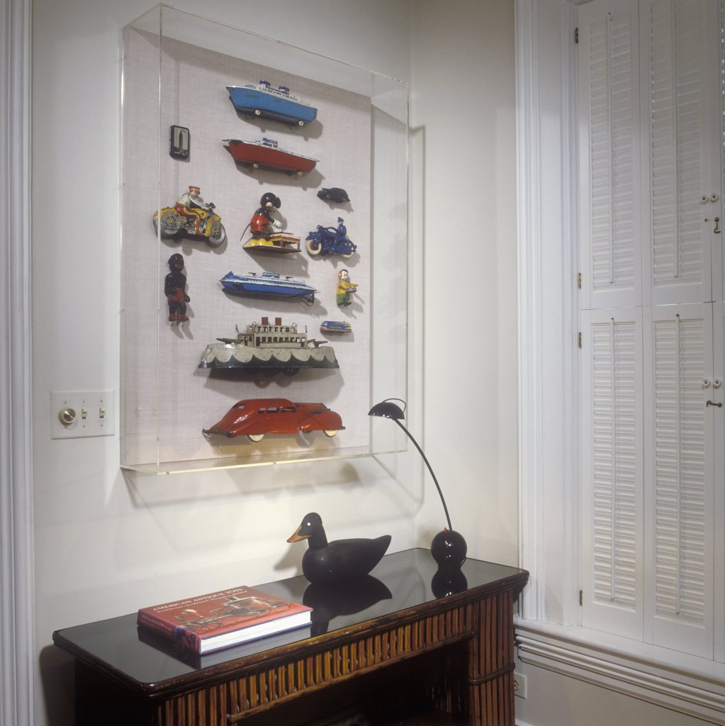 COLLECTION DISPLAYS: Antique toys, boats, and cars, metal from early 1900's to 1940's. Encased in large Lucite box over a narrow table. : Stock Photo