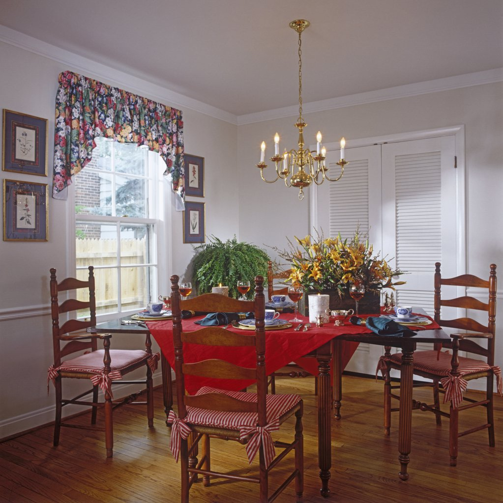 Stock Photo: 4053-10072 DINING AREAS: Fruitwood table and four ladder-back chairs, wood floors, red tablecloth, large floral arrangement, brass chandelier