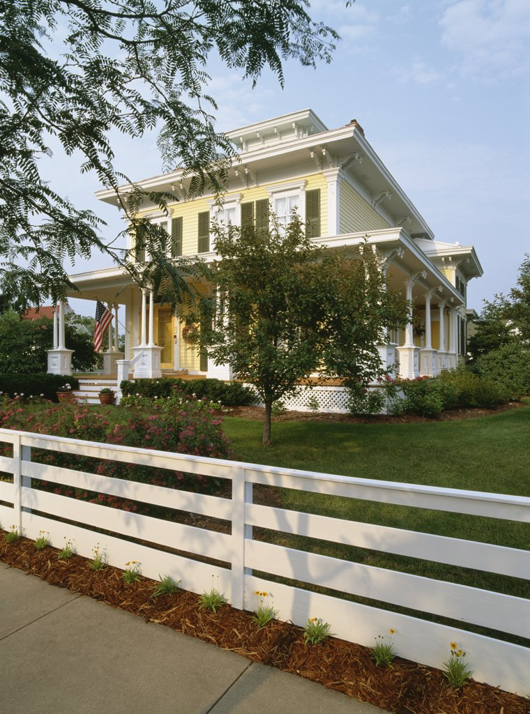 EXTERIORS: Victorian Italianate bracket house, angle view, white fence, wraparound porch, large yard, : Stock Photo