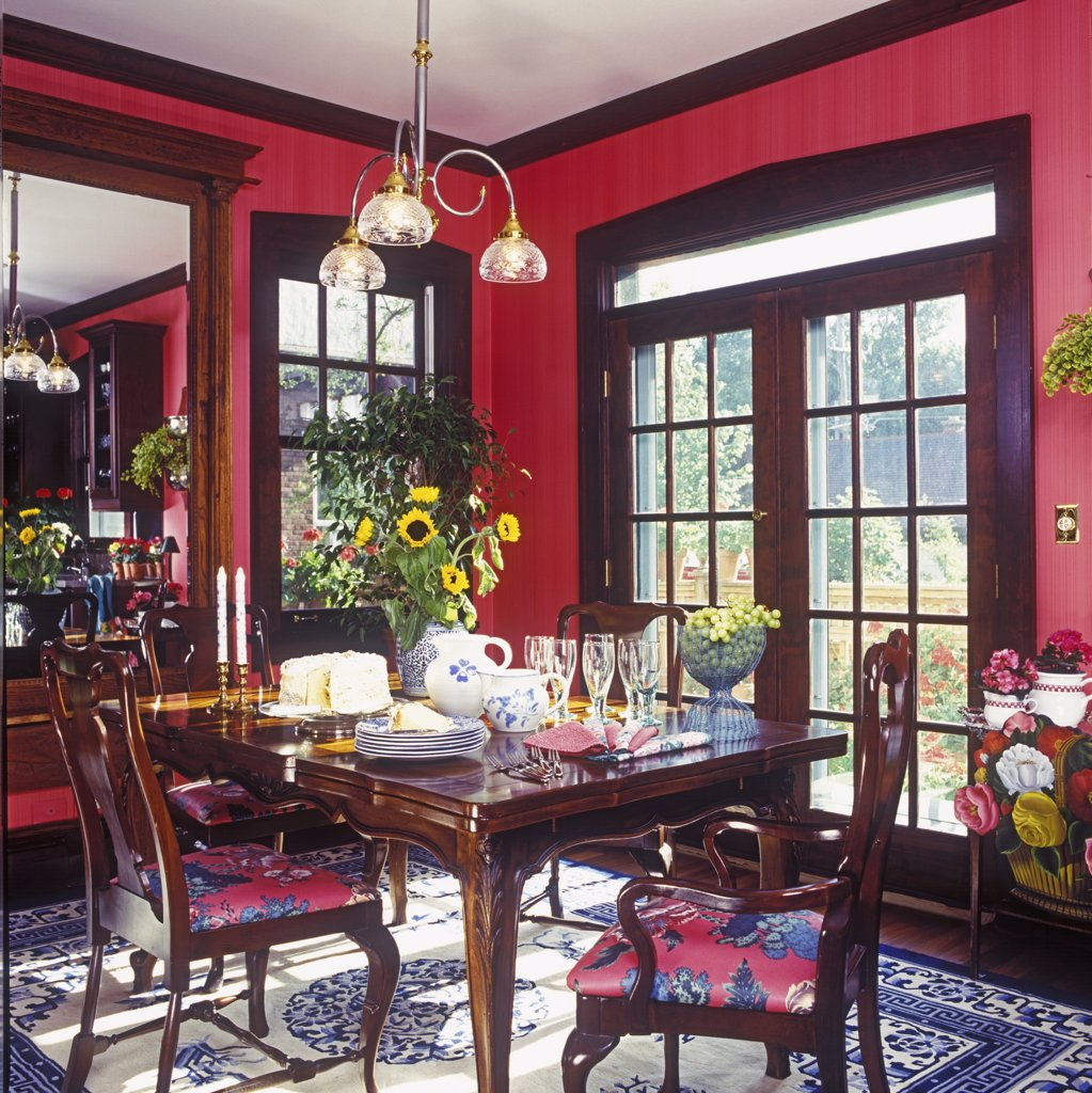 Stock Photo: 4053-10110 DINING ROOMS: Ruby-toned walls and dark trim. Patio doors, dark Chippendale style table and dining chairs, set for informal dessert, cake, grapes, sunflowers, focus tree, large entry hall type mirror, contemporary chandelier