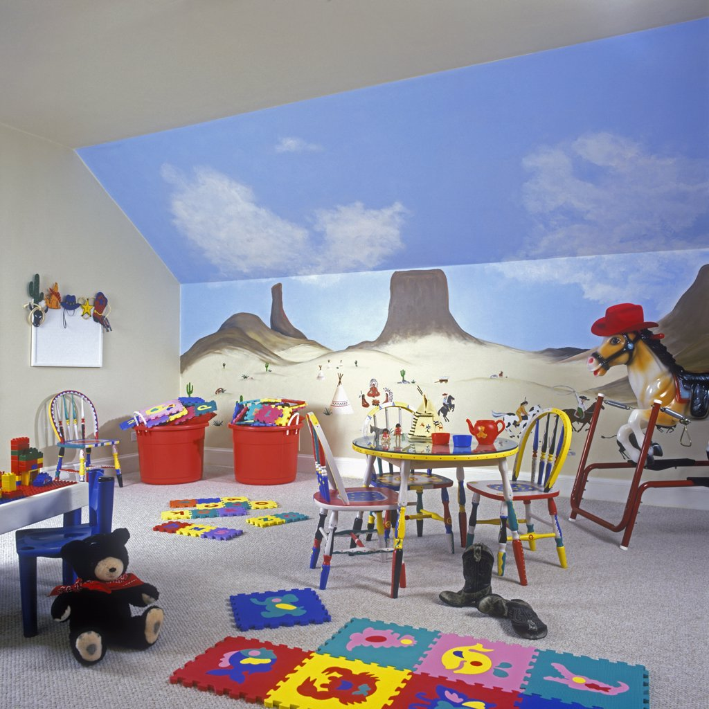 CHILDREN'S BEDROOM: Playroom in the attic. Painted mural on wall of southwestern scene. Table and chairs, and toys, riding horse on springs, teddy bear. : Stock Photo