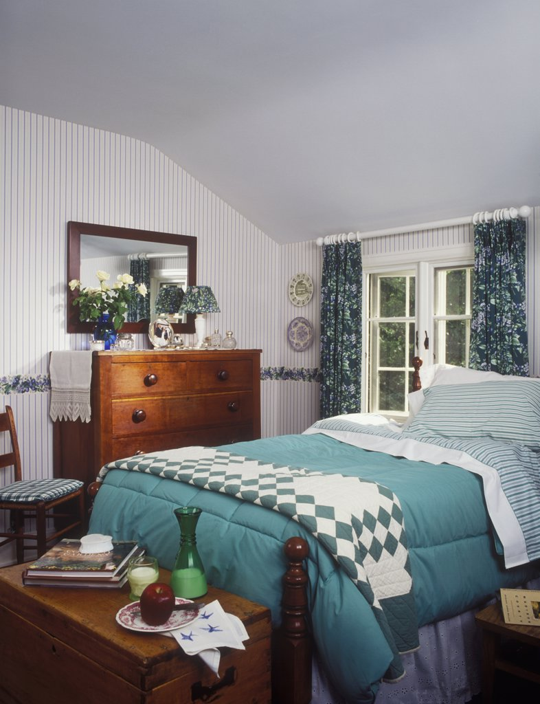 Stock Photo: 4053-10133 BEDROOM- Bed with green duvet. Wallpaper stripe, floral curtain, ring top, quilt, vintage dresser, wooden chest at foot of bed,