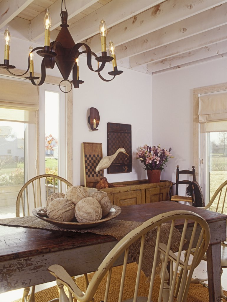 Stock Photo: 4053-10141 DINING AREA: Antique table and chairs. White country decor, tin chandelier, exposed beams, simple shades, distressed farm table, Windsor chairs, heron decoy, game boards.