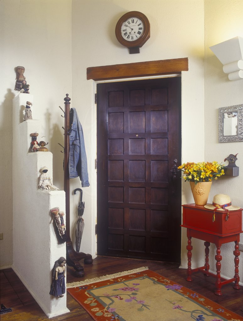 DOORS - Front entry door. Stucco house, adobe walls and graduated display ledge , ledge has collection of Native American dolls, Small red table, free standing coat rack with jean jacket, dark multi- paneled door, wall clock, area rug, wood floors, vase flowers : Stock Photo