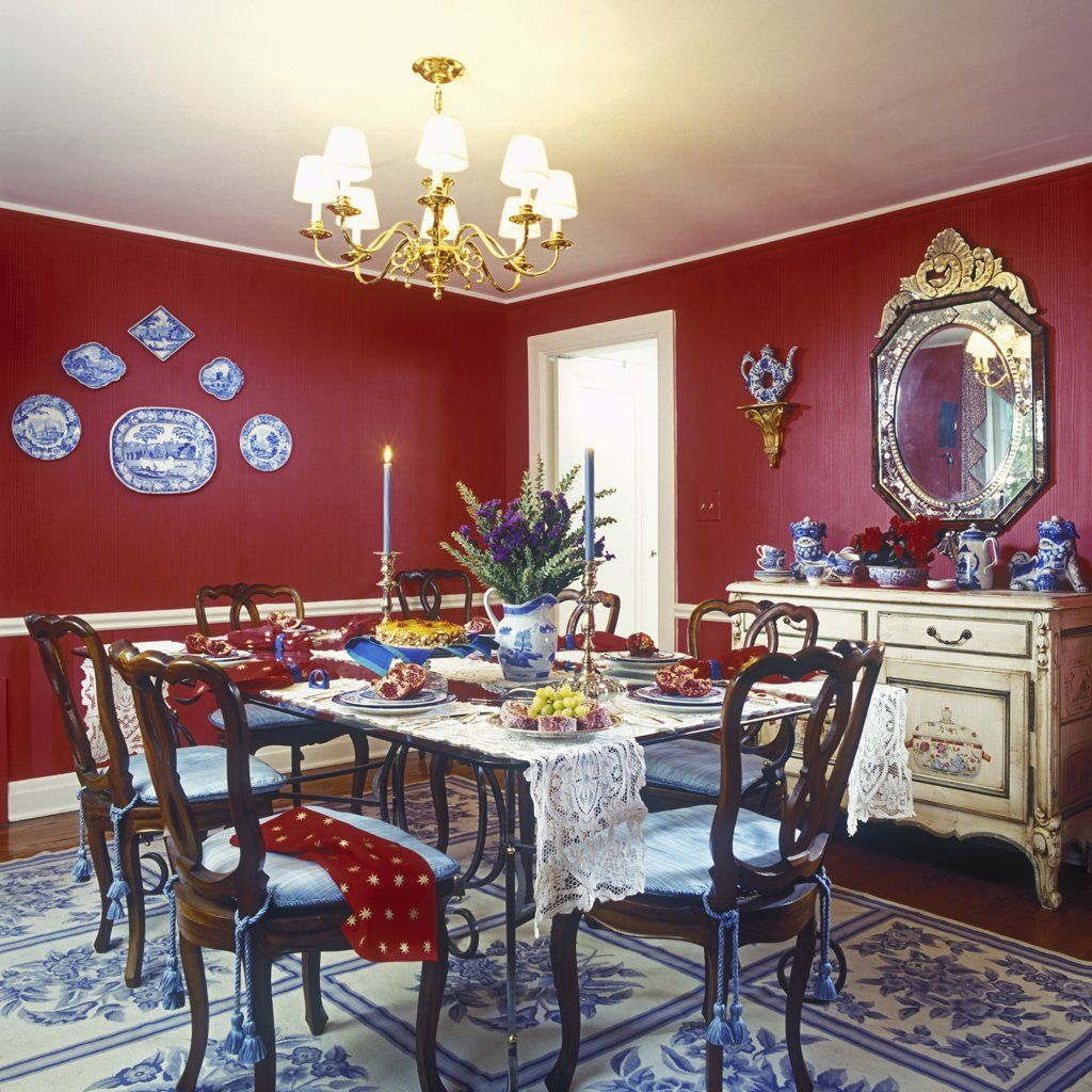 DINING ROOMS: Red walls, eclectic mix, white painted trim and chair rail, brass chandelier, blue and cream patterned area rug, plate display on wall, Venetian style mirror, painted dresser used as a sideboard, dessert and place settings, tassels hang from chairs : Stock Photo