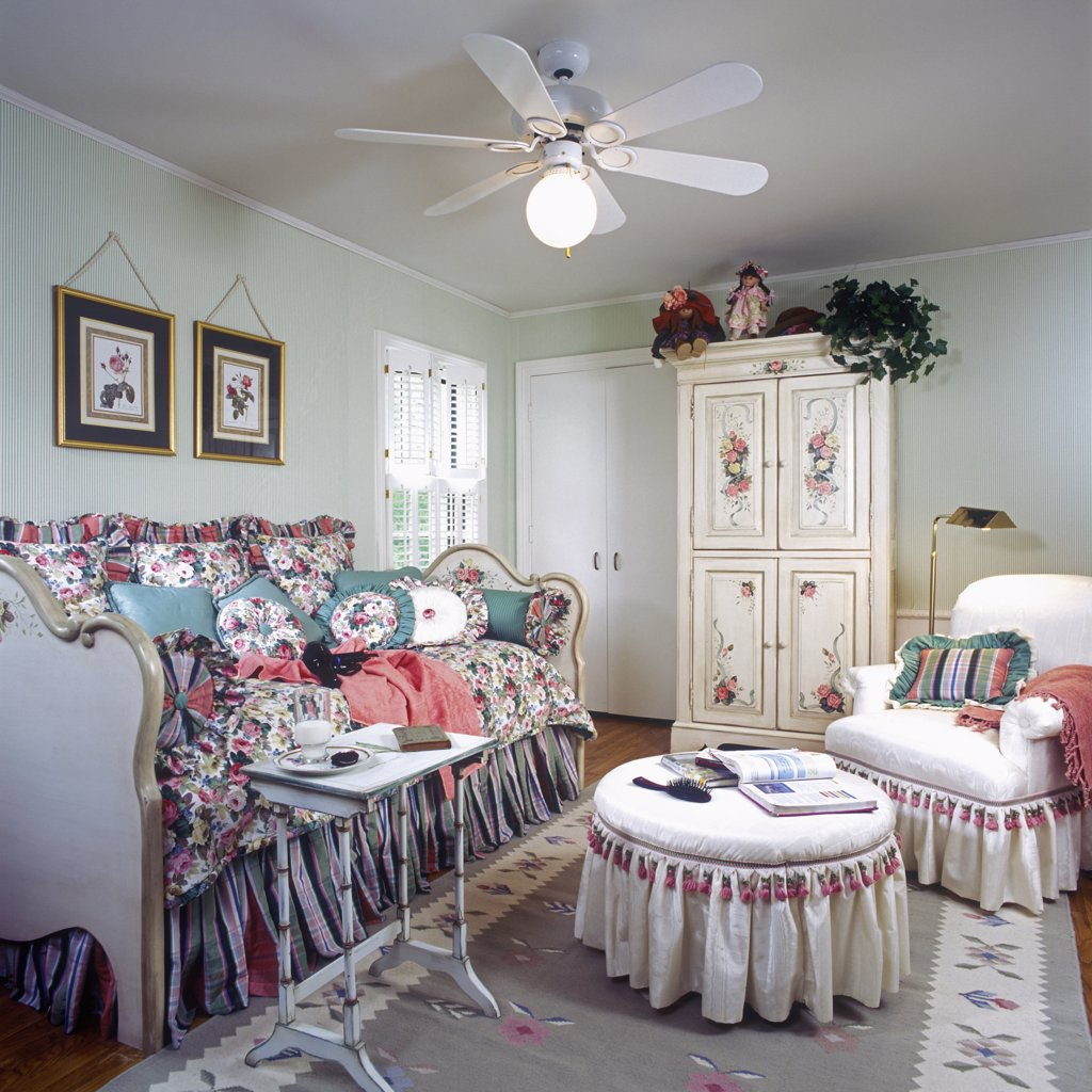 CHILDREN'S BEDROOM: Older girl's bedroom. Daybed with floral bedspread and pillows. Hand painted armoire. : Stock Photo