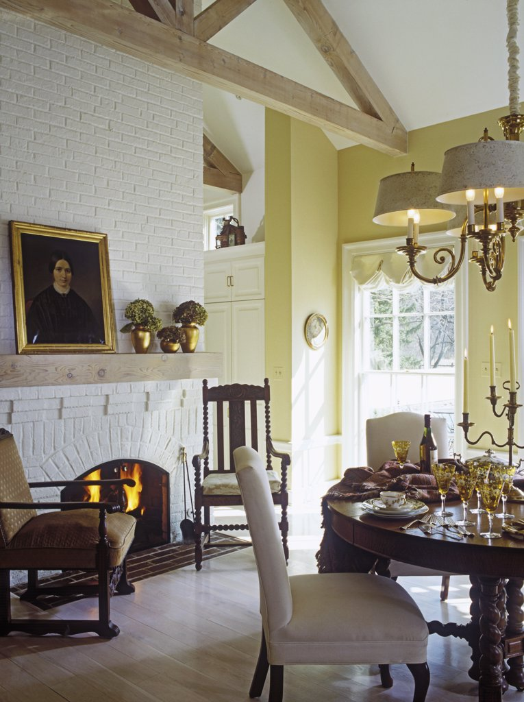 EATING AREAS: White brick fireplace, natural exposed beams, yellow walls, gold framed  17th century  portrait, gold vases filled with green hydrangea, barley twist table legs, white slipper chairs, elegant gold stemware, candelabra, place settings, chandelier with large shades, natural wood floors,  English style, period style, elegant, clean : Stock Photo