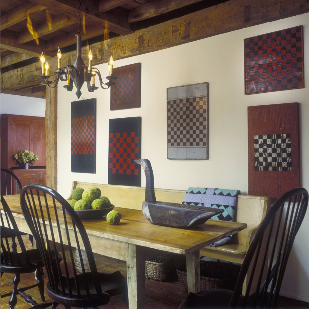 EATING AREA - Checkerboards on wall. Antique table, goose decoy, punched tin chandelier, bowl of hedge apples, bench , quilt, exposed beams, : Stock Photo