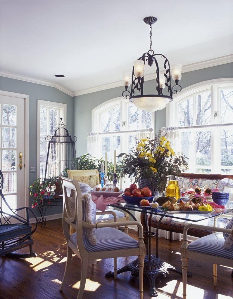 BREAKFAST AREA:  Sunroom, pale sage painted walls with white trim, crown molding, arched windows, cafe curtains, large floral on glass and iron table, eclectic mix of chairs, chandelier, table set with breakfast, wood floors : Stock Photo