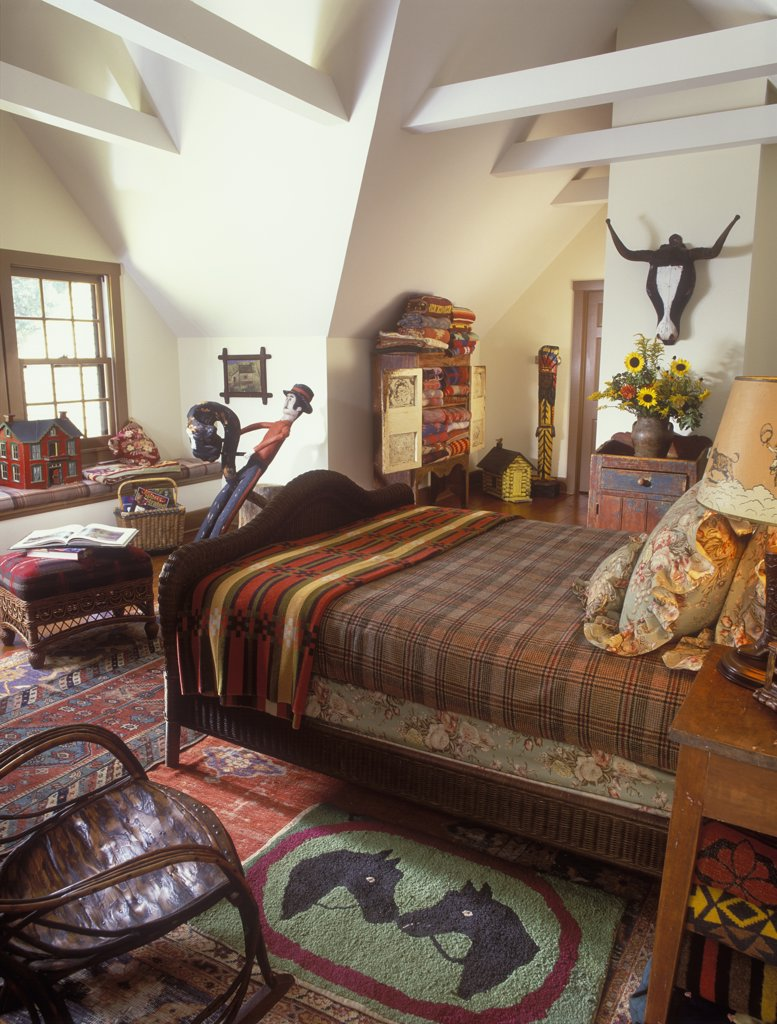 BEDROOM - Wicker bed. Folk art. Hooked rug. Horse pattern, floral and plaid bedding, cabinet filled with vintage blankets, wood folk art steer on wall, contemporary beams, red dollhouse, sunflowers : Stock Photo