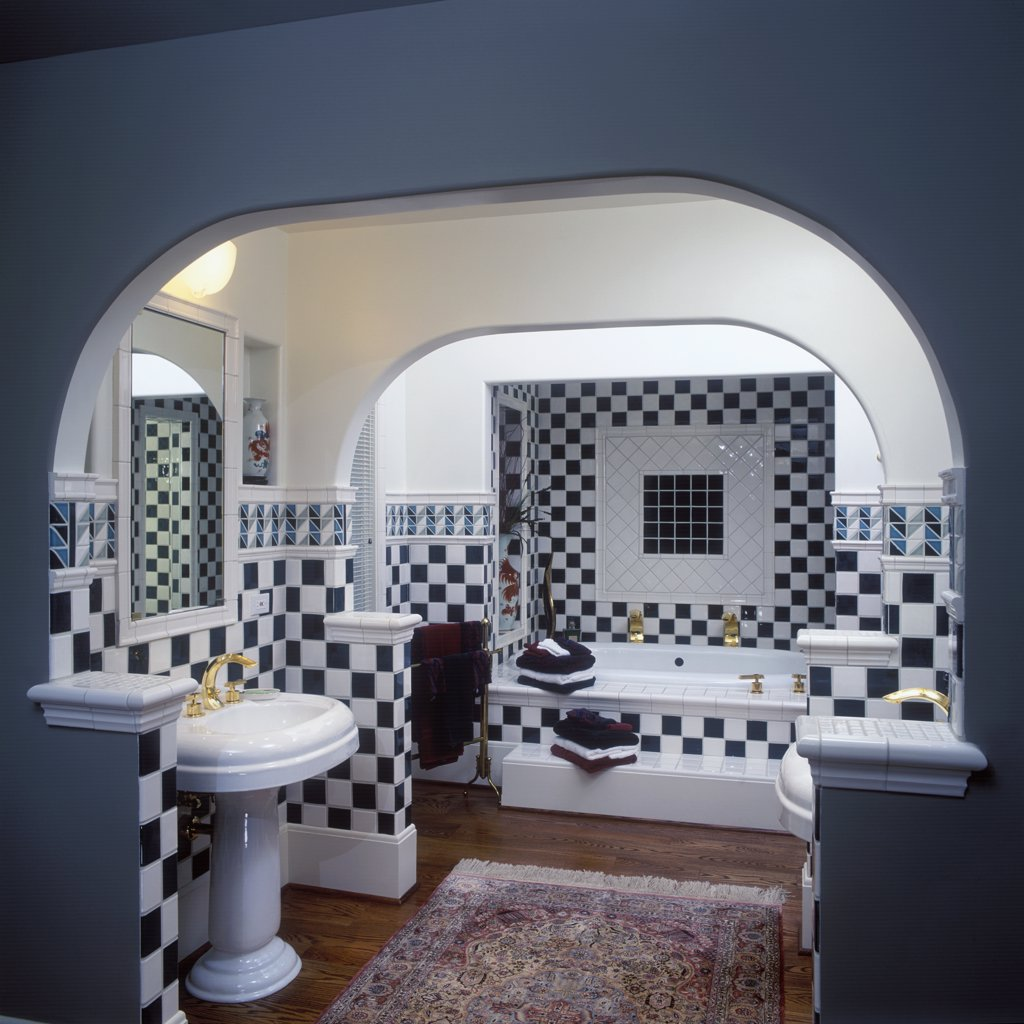 Stock Photo: 4053-10211 BATHROOMS: Contemporary. Dark green and white checkerboard pattern ceramic tiles on walls and above tub. Arched ceiling, painted dark grey wall in foreground, rest of walls white. White pedestal sink on left, tub in alcove in background. Wood floors, red Oriental rug.