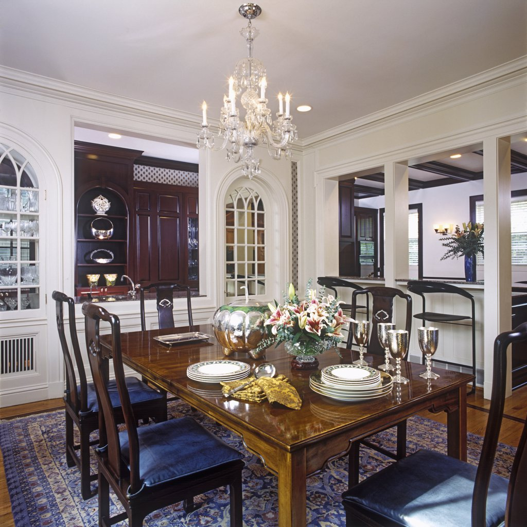 Stock Photo: 4053-10212 DINING ROOMS: Decorator Chinese style table and  chairs, dishes stacked on table. Arch to kitchen, two windows on either side of opening to kitchen area,  wet bar.