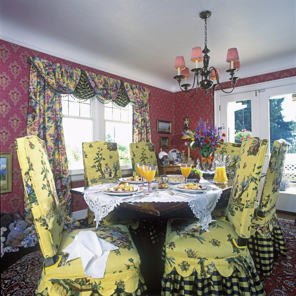DINING ROOMS: Yellow slip covered chairs, patterned swag drapes, red patterned wallpaper, French doors, table set for breakfast, : Stock Photo