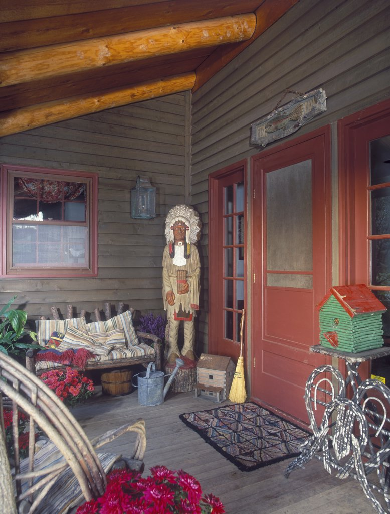 Stock Photo: 4053-10264 PORCHES - Life size wooden statue of Native American Indian chief. Red trim and door. folk art birdhouse, red mums.