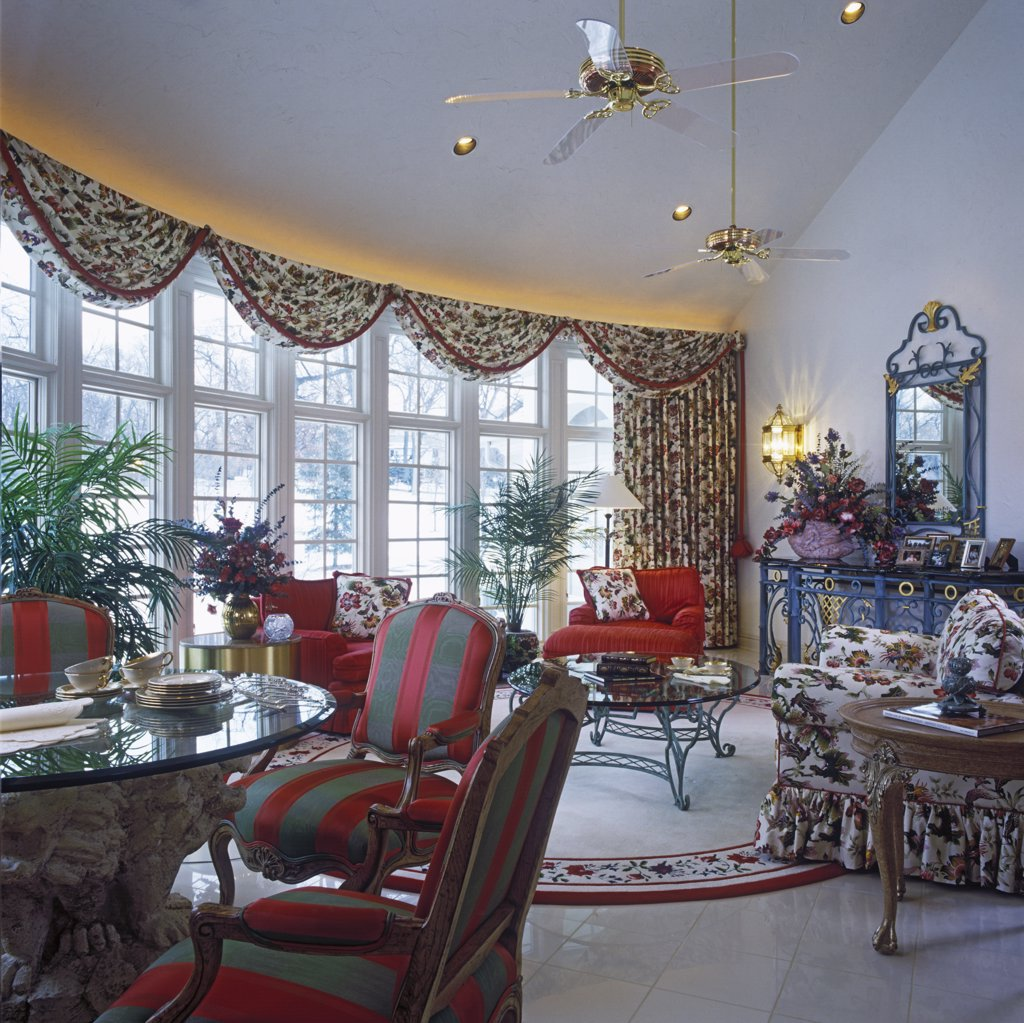 FAMILY ROOMS: Great room, cathedral ceiling, full length windows, eating areas off to left. Drapes with swag valance across top, curved wall of windows, marble tile floors, floral fabrics, striped Louis style chairs, glass top table with architectural base, hanging ceiling fans : Stock Photo