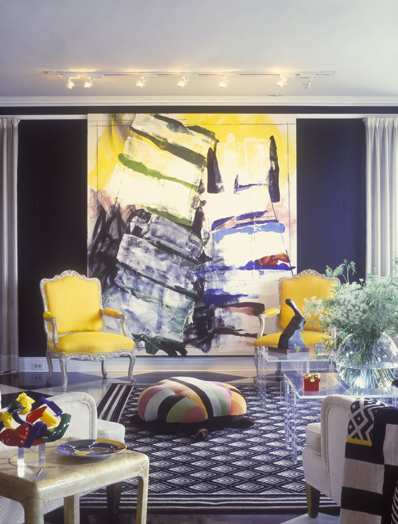 Stock Photo: 4053-10285 SITTING ROOM - Abstract art with yellow and black, bright yellow Louis XVI chairs, patterned black and white area rug, striped ottoman, Plexiglas tables, vase of Queen Anne's Lace, black painted walls, track lighting, foreground side table with glass sculpture, mixed styles, eclectic,