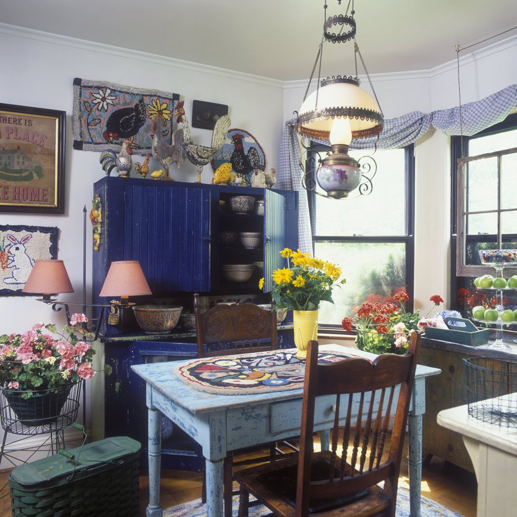 Stock Photo: 4053-10299 KITCHENS: Eclectic, vintage farm and folk art, distress painted cabinet in dark blue, distressed pale blue farm table, hooked rugs decorate the wall and table, vase flowers, geraniums in wire baskets, pressed back chairs, sponge ware bowls in cupboard, stacked glass cake plates hold green apples, architectural salvaged window hangs in window, swagged window treatments, hanging antique oil lamp converted to electric, collection of folk art roosters