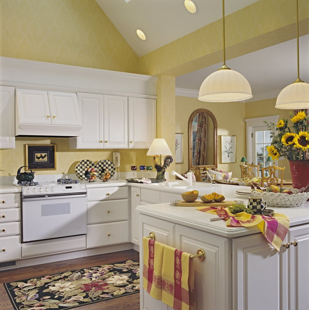 KITCHENS - Cathedral ceiling, pale gold walls, white cabinetry, brass door pulls and towel racks, black and white checkered plates, roosters, molding, sunflowers, : Stock Photo
