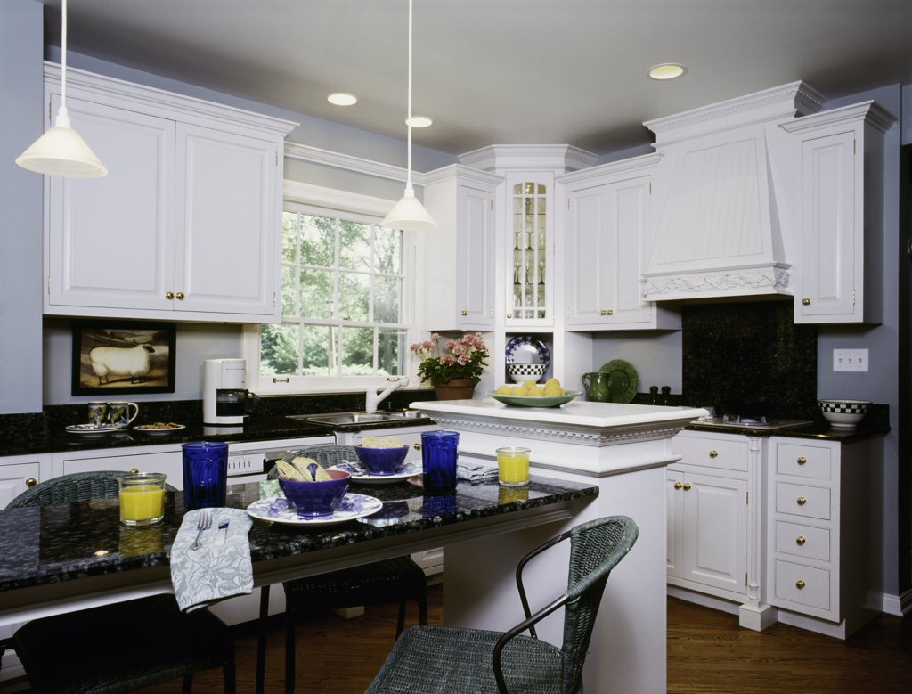 KITCHEN: eating area, black granite counters,  wicker chair, recessed lighting pendant lights,, sink area, potted geranium by window, sheep picture, architectural detailed : Stock Photo