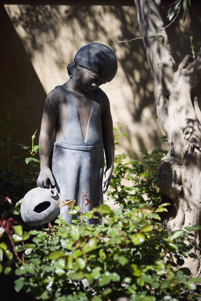 Stone boy statue in landscaping : Stock Photo