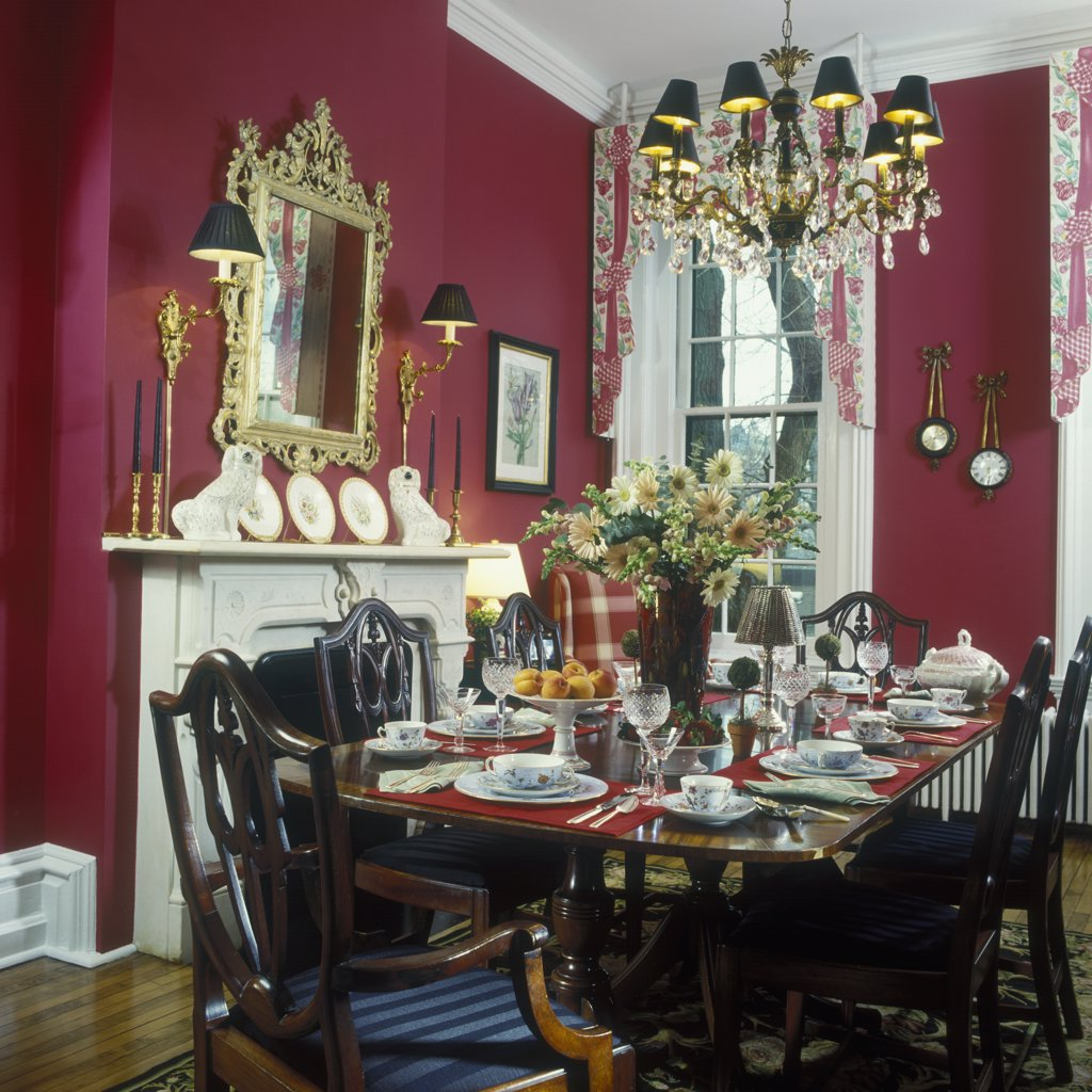 DINING ROOM: Formal rectangular mahogany table, Hepplewhite style chairs, crystal and brass chandelier with black shades, wall sconces with shades, gold gilt mirror over fireplace, red walls. tall windows with floral cornices, place settings, gerbera daisy floral arrangement, Chelsea dogs, wood floors : Stock Photo
