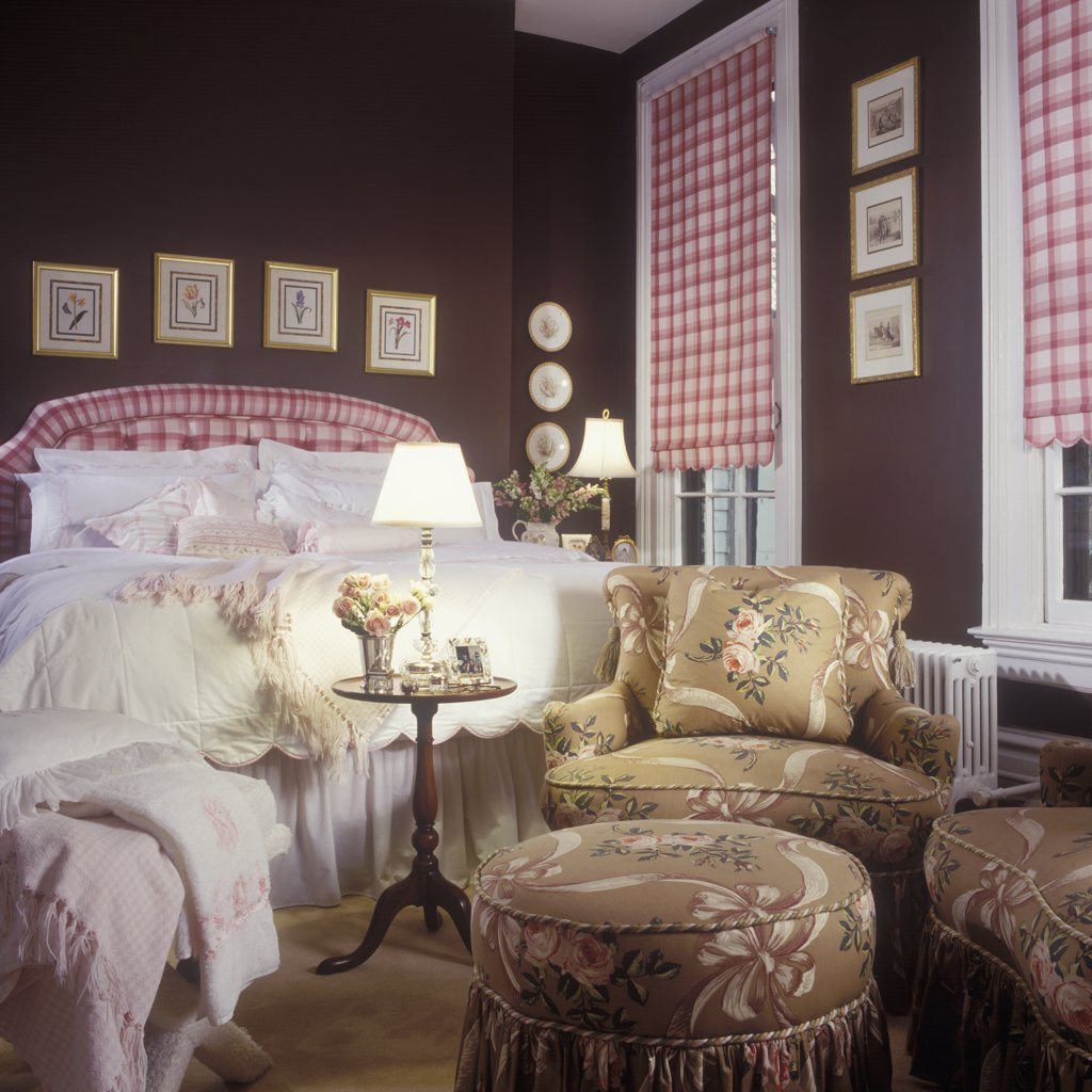 BEDROOMS - Master bedroom with brown walls. Pink plaid shades and headboard, white bedding, white trim, taupe upholstered arm chairs and round ottoman, radiator : Stock Photo