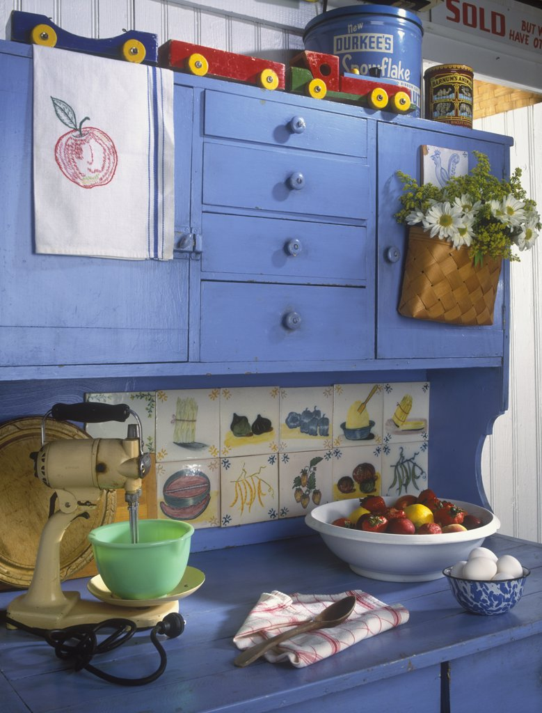 Stock Photo: 4053-10477 KITCHEN - Vacation home. Blue painted Hoosier style cupboard, antiques, vintage mixer with jadeite bowl, wooden toys, old tins, colorful, bowl of strawberries, painted tiles