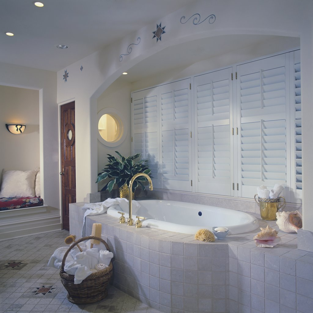 BATHROOM - Tub with tile surround set in arched alcove with shuttered windows, round window. Basket of towels on tile floor, southwest designs, round window, : Stock Photo